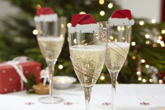 three champagne glasses with Santa Clause hats.